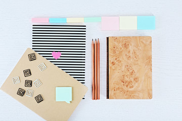 Notebooks with clips, stickers and pencils on a white table