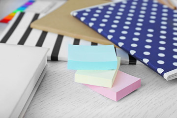 Notebooks with coloured stickers on a white table