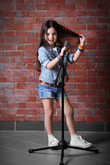 Beautiful little girl with microphone on brick wall background
