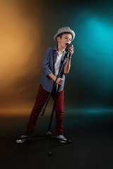 Little boy singing with microphone on a dark lighted background