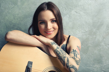 Woman with tattoo and guitar sitting on grey background