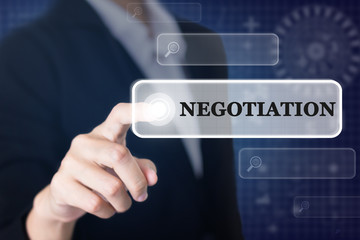 Businessman pressing a NEGOTIATION concept button. Can be used in advertising.