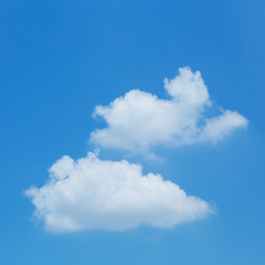 fluffy white cloud floating on clear blue sky background