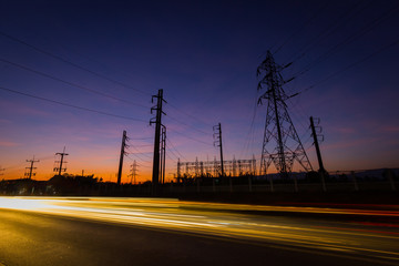 silhouette electricity pylons and power plant with light trails