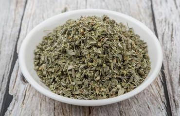 Marjoram herbs in white bowl over wooden background