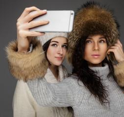 Two girls in winter gur hats taking selfie picture.