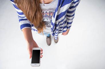 Frau hält ein Smartphone / Tablet mit leerem Display