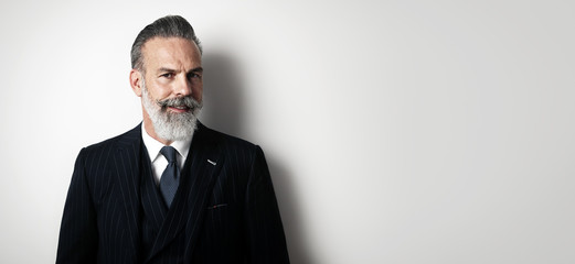 Portrait of bearded gentleman wearing trendy suit and smiling against the empty wall. Wide
