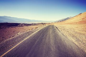 Vintage filtered empty desert road.