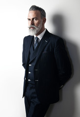 Portrait of bearded businessman wearing trendy suit and stands against the empty white wall. Vertical
