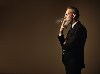Portrait of smoking gentleman wearing trendy suit and stands against the empty wall. Horizontal