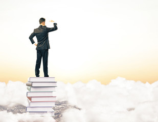 Businessman on pile of books among clouds and looking into the d