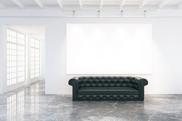 Blank poster on the wall in loft room with black leather sofa an
