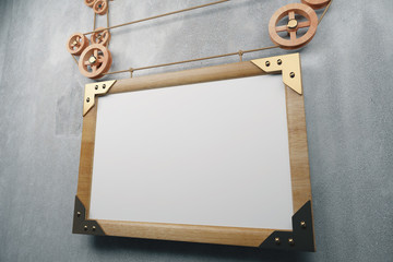 Blank wooden picture frame in steampunk style on concrete wall,