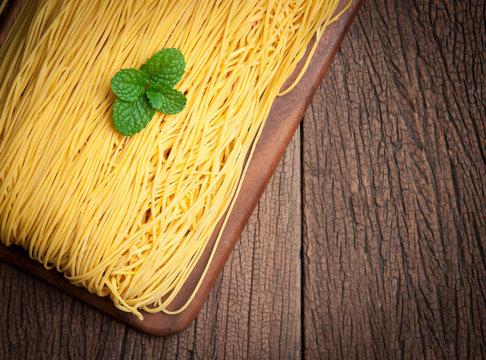 Egg noodles on wood background