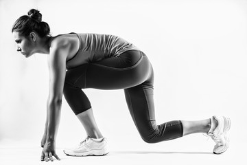 Fit female athlete ready to run over grey background. Female fitness model preparing for a sprint