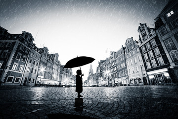 Fototapete - Child with umbrella standing alone on cobblestone old town in rain
