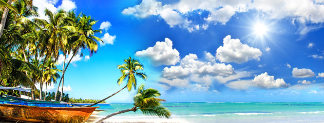 Beach panorama: Perfect tropical paradise beach with turquoise blue water, blue sky, fisherman boat...