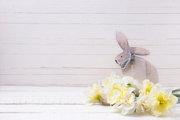 Yellow narcissus flowers and decorative Easter rabbit   on white