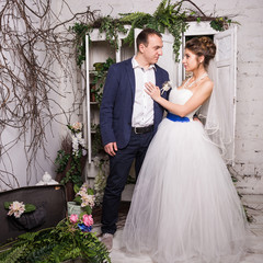 Young wedding couple posing in white decorating studio