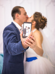 Wedding couple doing selfie on smart-phone in white studio