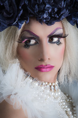 Drag queen with spectacular makeup, glamorous trashy look, posing serious facial expression