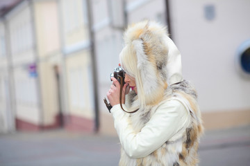Hipster girl with vintage camera. positive girl in a fur cape photographed using vintage camera. Outdoors lifestyle