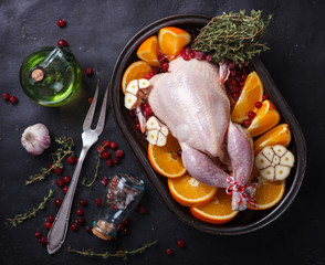 Raw chicken with oranges and cranberries .selective focus.