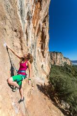 Hippie Style Female Climber ascending Vertical Orange Rock