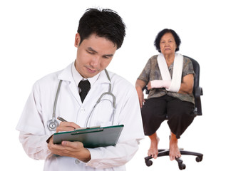 doctor writting medical report with senior woman injured arm