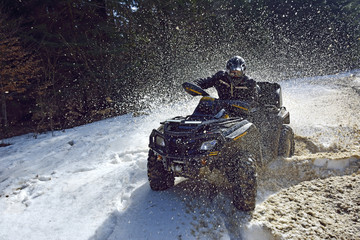 man driving a quad bike in the winter field