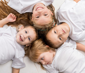 smiling children lying with their heads together