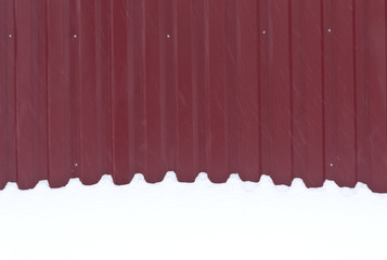 Red metal fence in snow.