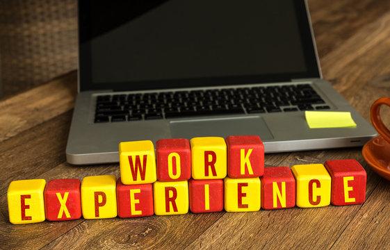 Work Experience written on a wooden cube in a office desk