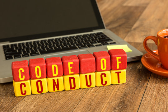 Code of Conduct written on a wooden cube in a office desk