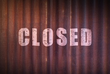 Closed sign on old zinc sheet rust background.