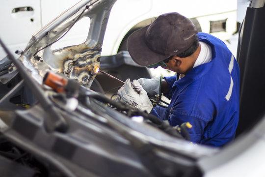 Man mechanical worker repairing a car body in a garage