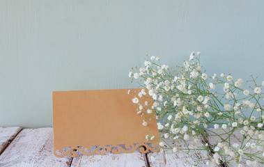 fresh white flowers next to vintage empty card over wooden table. vintage filtered and toned image
