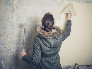 Young woman stripping wallpaper