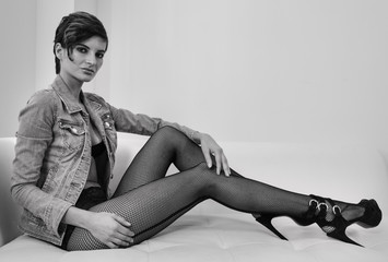 Picture of female model sitting on the sofa and showing legs in fishnet hosiery