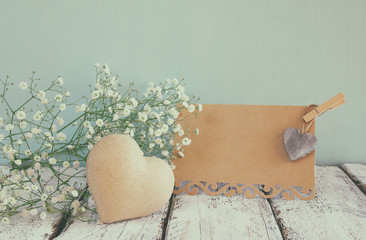 fresh white flowers, heart next to vintage empty card over wooden table.