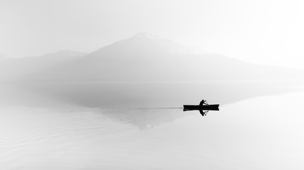 Fog over the lake. Silhouette of mountains in the background. The man floats in a boat with a...