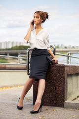 Young fashion business woman with handbag calling on mobile phone