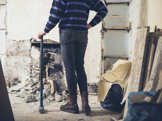 Woman standing by fireplace with sledge hammer