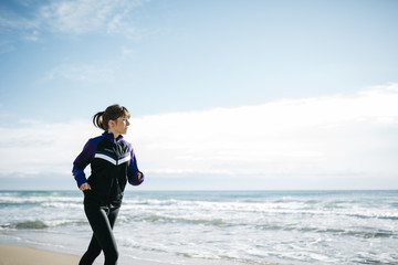 Young beautiful woman running on the beach. Fitness caucasian gi