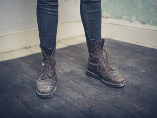 Person wearing boots standing in empty room