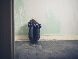 Sad young woman sitting on floor in empty room