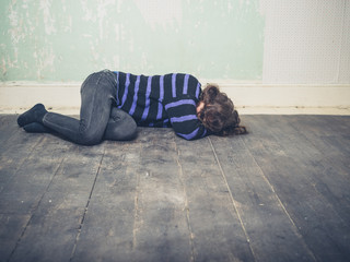 Sad young woman lying on floor