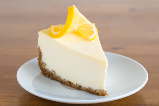 Cheesecake on white plate on wooden background decorated with lemon slice