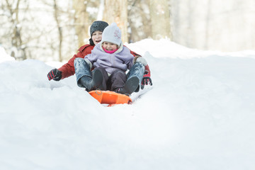Two excited siblings shouting during winter downhill ride on plastic winter snow slider
